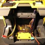 Blick unter das Fahrerhaus und die vordere Platine, alle Funktionen des Fahrerhauses sind hier angeschlossen, links daneben in Gelb das Lautsprecherkabel, rechts der Datenbus, die Motorleitungen und das Kabel zum Lenkservo