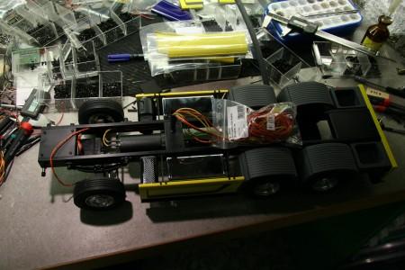 Aufblick auf den Rahmen bei der Endmontage, die Kabel in der Mitte gehen zu r Steuereinheit im Aufbau, das dreipolige Kabel an der Vorderachse versorgt alle Funktionen im Fahrerhaus, die schwarze Box vor der Vorderachse beherbergt den Lautsprecher